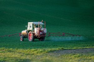 truck spraying herbicides/pesticides in field of green grass